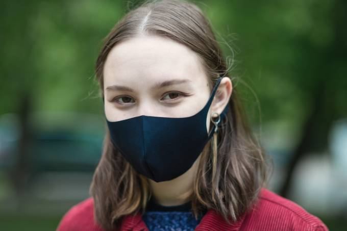 Cute teenage girl smiling behind protective mask outdoors