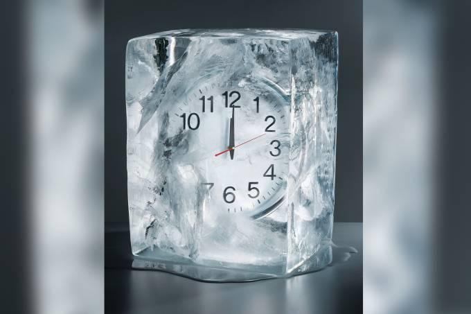 Alarm clock frozen in ice, close-up
