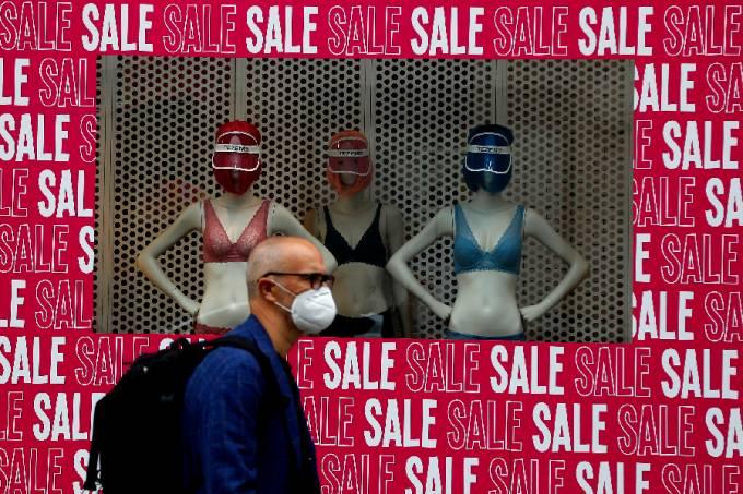 Homem de máscara em frente a vitrine em Londres