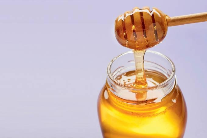 Honey dipper with liquid honey in jar on purple background