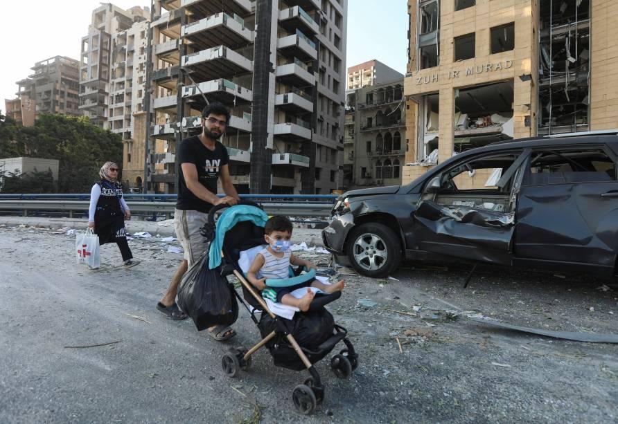 Homem passeia com criança em área próxima ao local da explosão na capital libanesa - 05/08/20020
