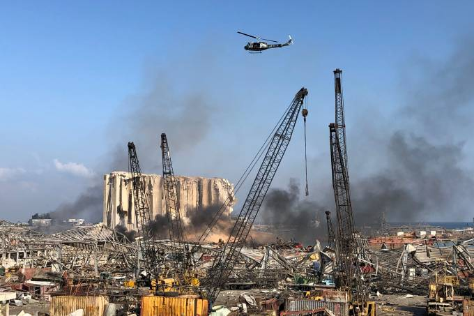 A Lebanese army helicopter flies over the site of Tuesday's blast in Beirut's port area