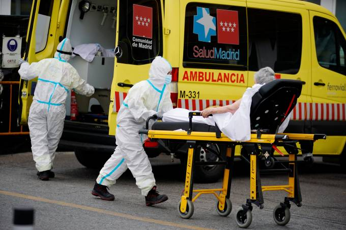 A healthcare worker wearing protective gear pushes a stretcher with a patient near the emergency unit of the 12 de Octubre hospital during the coronavirus disease (COVID-19) outbreak in Madrid
