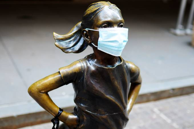 Fearless girl art installation stands in front of the New York Stock Exchange wearing a mask