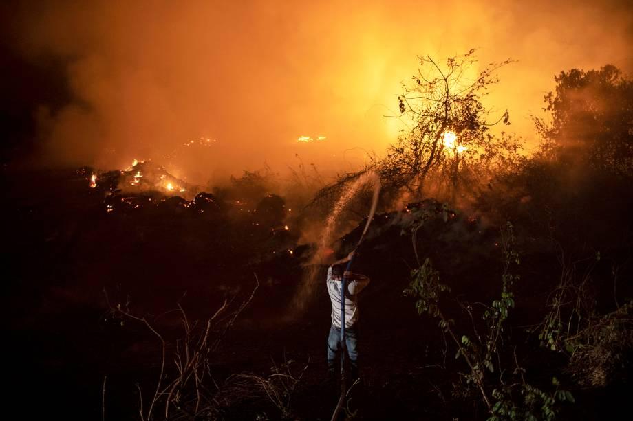 TRANSPANTANEIRA Voluntários tentam apagar o fogo em uma das 119 pontes da madeira da região, no Mato Grosso