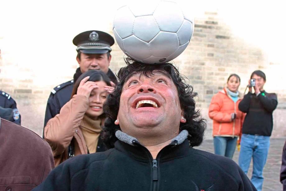 Diego Maradona joga com uma bola enquanto visita a Grande Muralha da China, em 2003 -