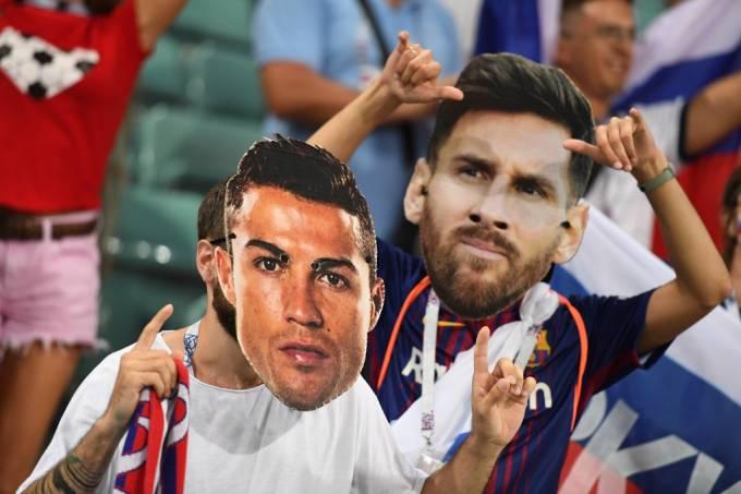 Torcedores com máscaras de Cristiano Ronaldo e Lionel Messi