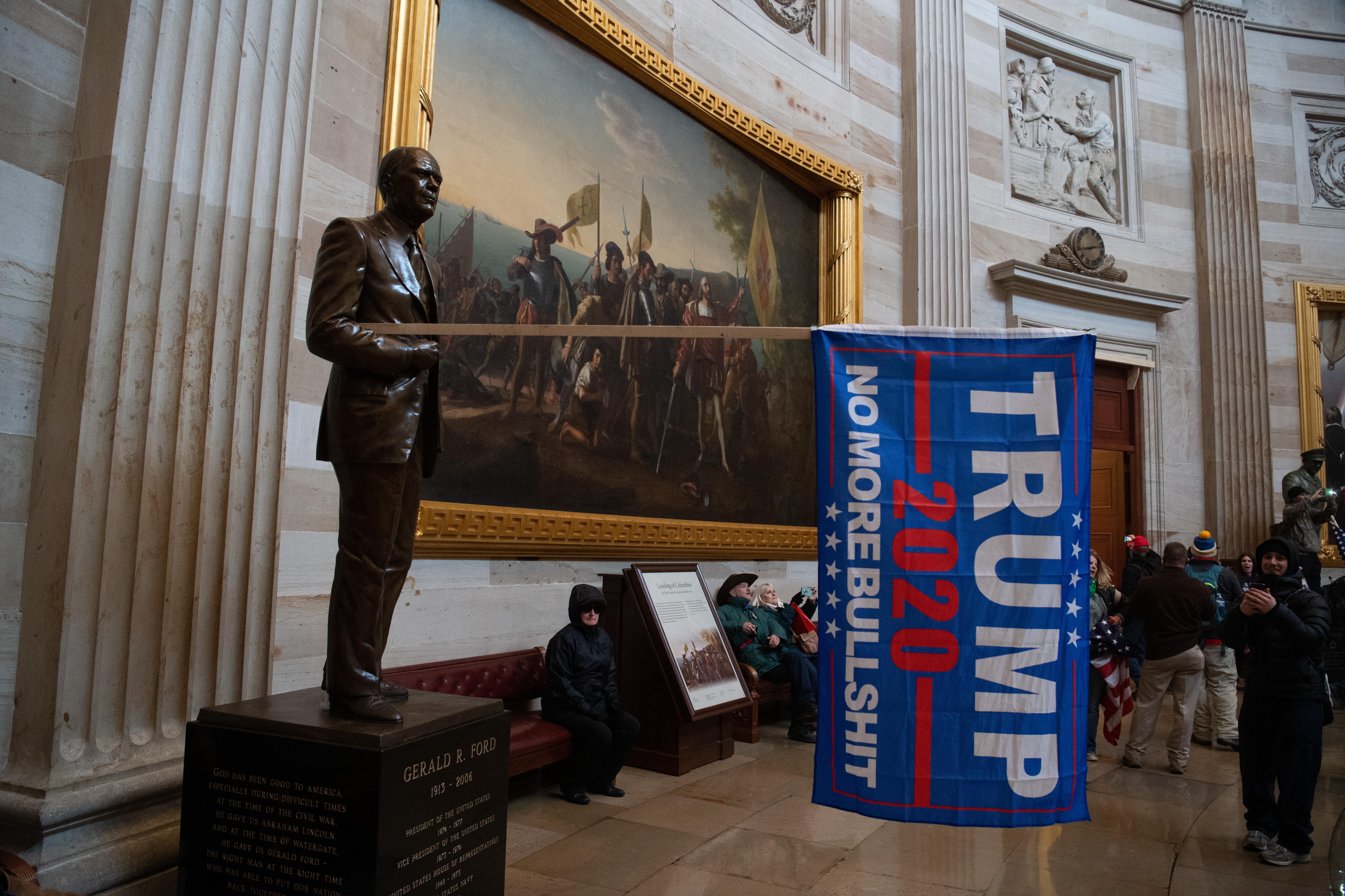 Estatátua adornada com bandeira de Donald Trump durante invasão ao Capitólio, quadro ao fundo em exposição na Rotunda