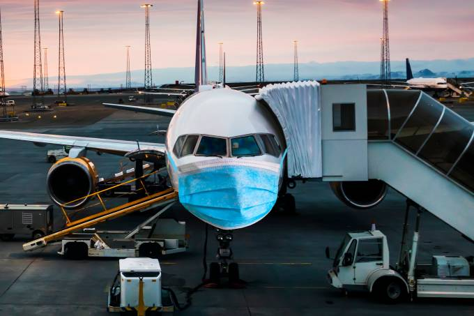 Airplane in a medical mask. Air Travel Crisis Concept