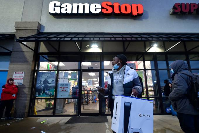 A man wearing a face mask leaves Game Stop with the new