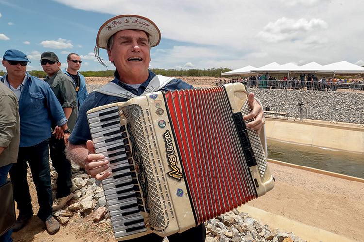 Jair Bolsonaro tocando instrumento, sanfona.