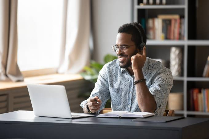 African guy learn online wearing headset looking at laptop screen