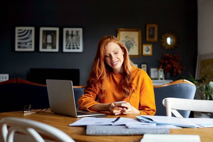 Smiling businesswoman using mobile phone at home