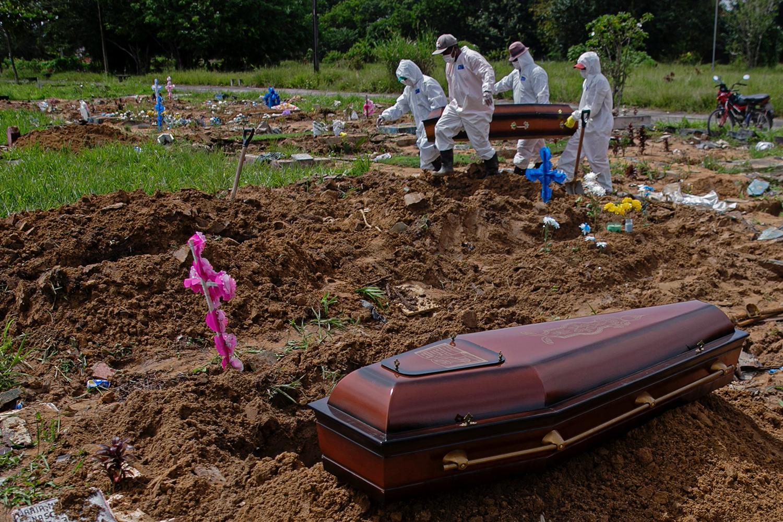 Coveiros do cemitério público Parque Tapana carregam o caixão de uma vítima de COVID-19 antes de enterrá-lo, em Belém, no estado do Pará -