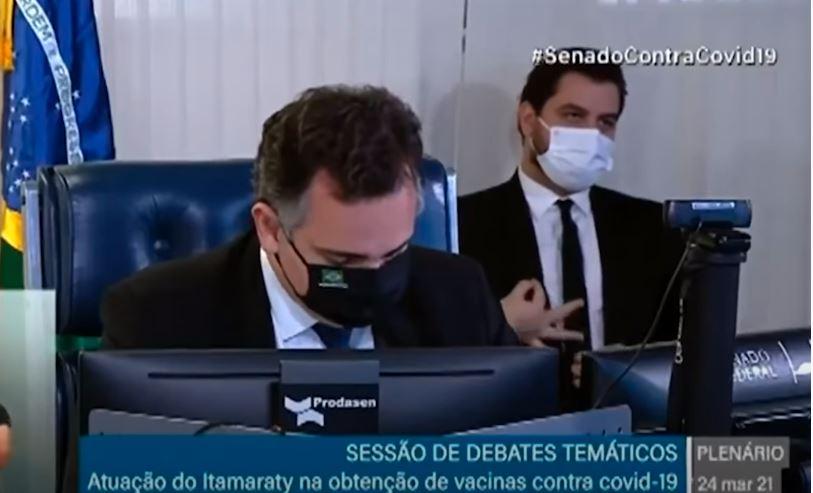 O assessor internacional de Bolsonaro, Filipe Martins, faz gesto considerado supremacista enquanto o presidente do Senado, Rodrigo Pacheco (DEM-MG), falava