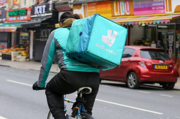 A Deliveroo cyclist riding with a package in London