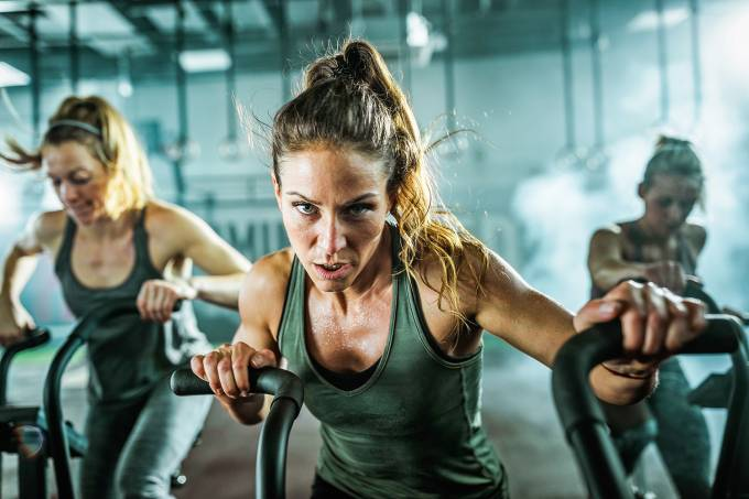 Determined athletic woman during exercise class on bike in a gym.