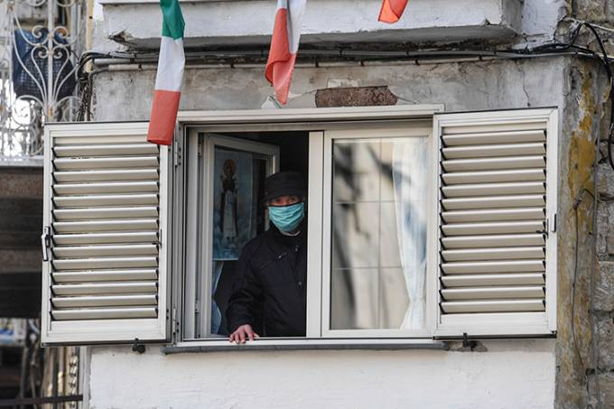 Elderly man wearing a protective mask looks out of a window