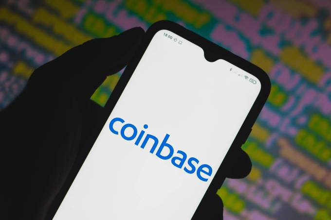 In this photo illustration a Coinbase logo seen displayed on
