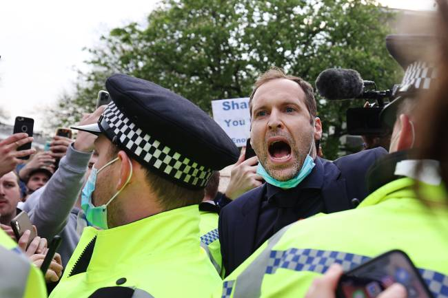 O ex-goleiro do Chelsea, Petr Cech, pede calma enquanto os torcedores se reúnem para protestar contra a introdução da Superliga Europeia, em Londres -