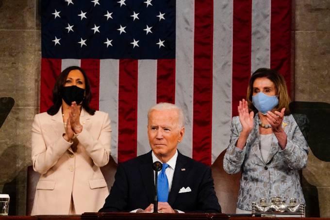 O presidente dos EUA, Joe Biden, em primeiro plano. Ao fundo, à esquerda, a vice, Kamala Harris, e, à direita, a Presidente da Câmara dos Representantes, Nancy Pelosi – 28/04/2021 –