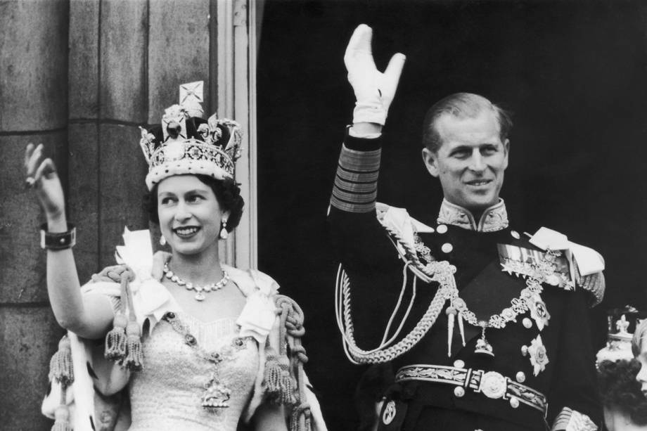 A rainha Elizabeth II e o duque de Edimburgo acenam para a multidão na varanda do Palácio de Buckingham, em 1958 -