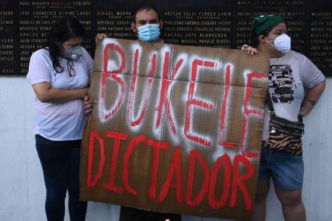 "Demonstrators hold a sign reading ""Bukele Dictator"", referring to Salvadoran Prsident Nayib Bukele"