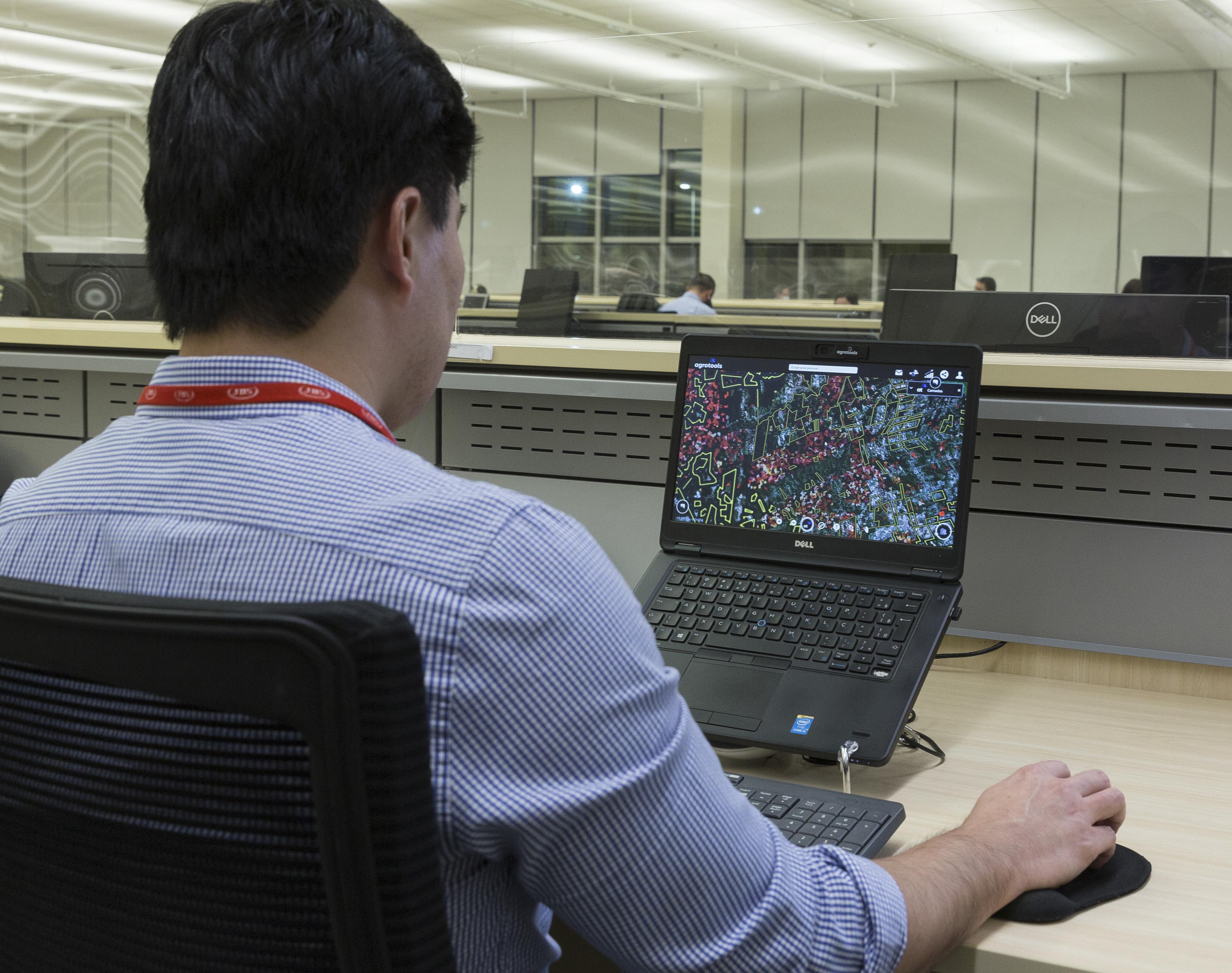 Homem de costas, sentado em frente a um computador