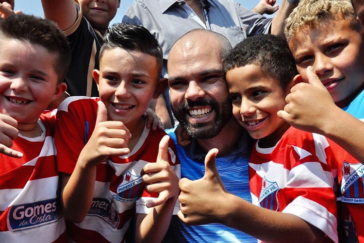 O prefeito de São Paulo posa para foto com crianças durante inauguração da Arena Cratera, na região de Parelheiros, em 2019 -