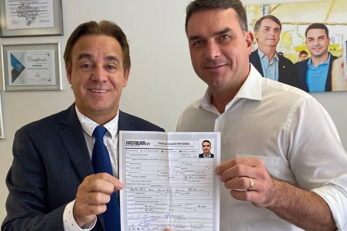 O presidente do Patriota, Adilson Barroso, e Flávio Bolsonaro exibem ficha de filiação do senador ao partido