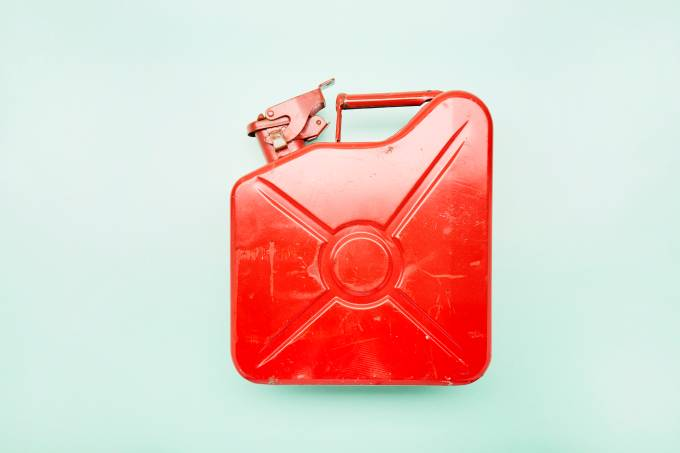Directly above shot of red oil canister on turquoise background
