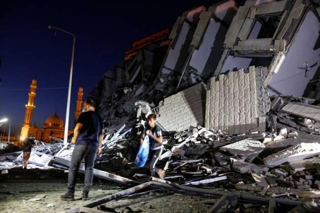 Palestinos reúnem-se em frente a um prédio de 13 andares destruído por Israel