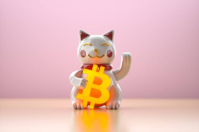 Toy cat holding glowing bitcoin sign