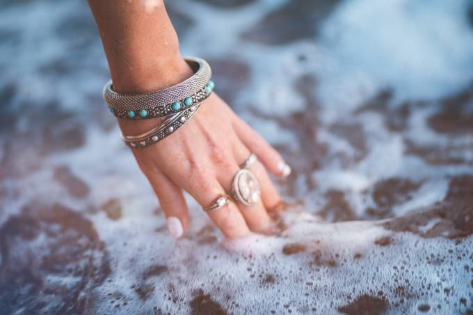 Young woman with boho style jewelry at the beach