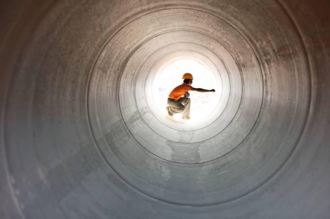 Construction worker inspecting pipeline in desert