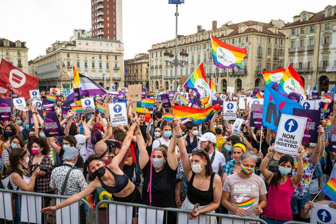 General view shows demonstrators hold placards and rainbow