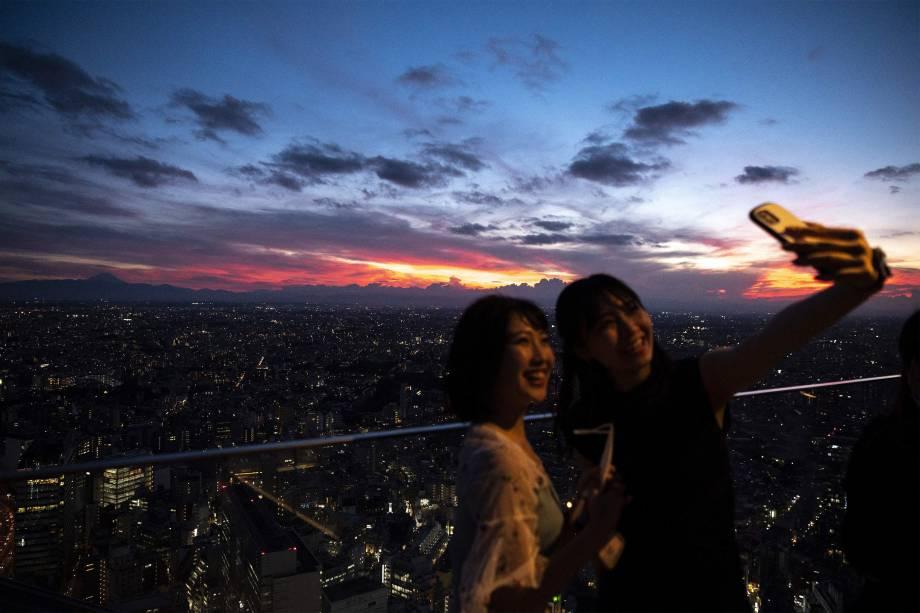 Mulheres posam para foto com o Monte Fuji ao fundo durante as Olimpíadas de Tóquio 2020 -