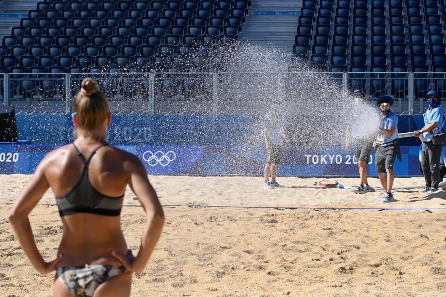 Trabalhadores borrifam água em quadra de vôlei de praia durante os treinos -