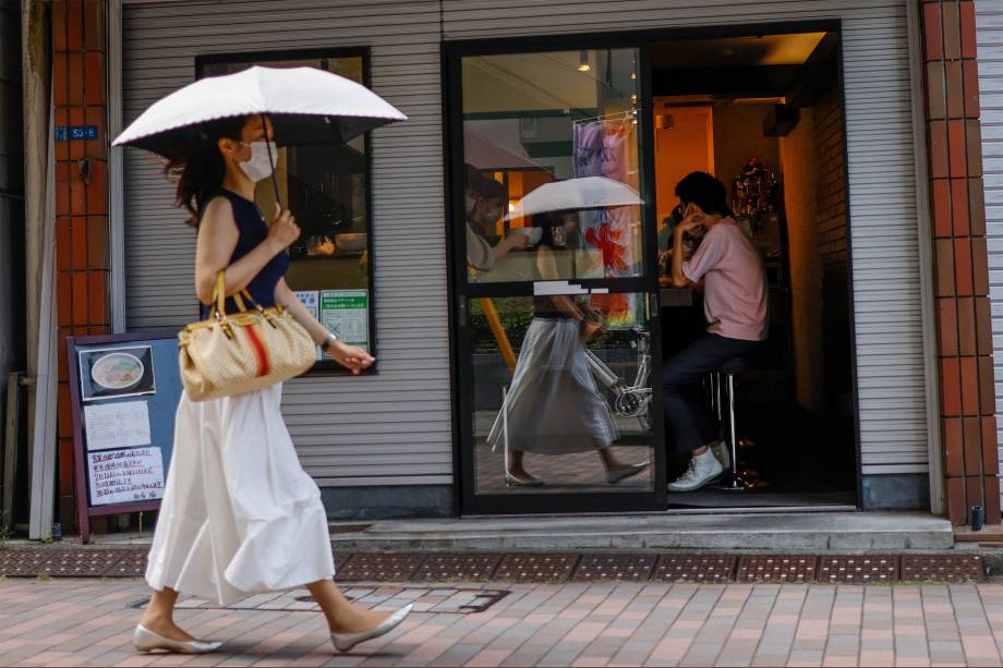 Pedestre passa em frente a restaurante em Shinagawa, Tóquio -