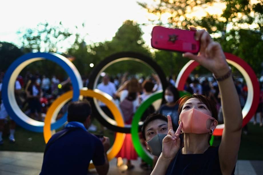 Pessoas fazem selfie em frente aos anéis Olímpicos durante a cerimônia de abertura das Olimpíadas 2020, em Tóquio -