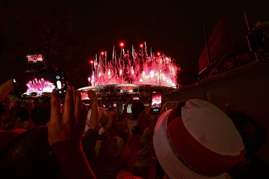 Apoiadores do lado de fora tiram fotos dos fogos de artifício iluminando o céu sobre o Estádio Olímpico -