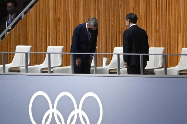 President of the International Olympic Committee (IOC) Thomas Bach (L) salutes Japan's Emperor Naruhito (R) as they attend the opening ceremony of the Tokyo 2020 Olympic Games, at the Olympic Stadium, in Tokyo, on July 23, 2021. (Photo by Martin BUREAU / AFP)