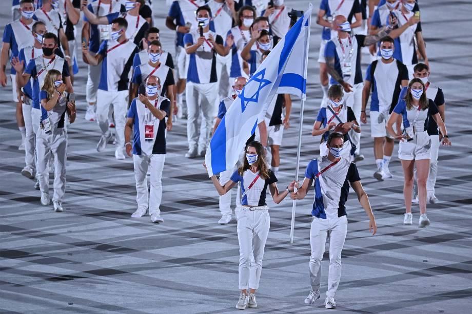 Hanna Minenko e Yakov Toumarkin carregam a bandeira de Israel e lideram a delegação na cerimônia de abertura dos Jogos Olímpicos de Tóquio, no Estádio Olímpico -