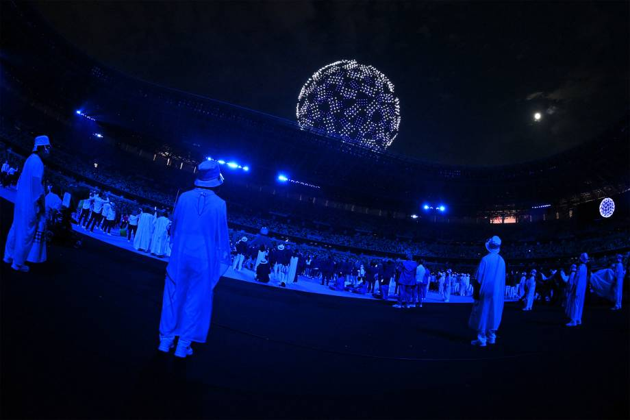 Atletas e voluntários olham drone no céu durante a cerimônia de abertura das Olimpíadas 2020, no Estádio Olímpico de Tóquio -