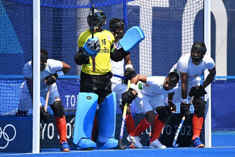 O goleiro Sreejesh Parattu Raveendran, da Índia, e seus companheiros de equipe defendem uma cobrança em partida contra a Nova Zelândia -