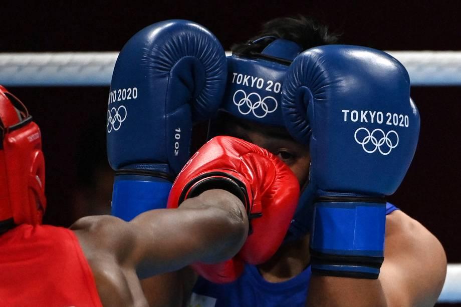 O boxeador Marcelat Sakobi Matshu, da República Democrática do Congo, durante soco em Nesthy Petecio, das Filipinas -