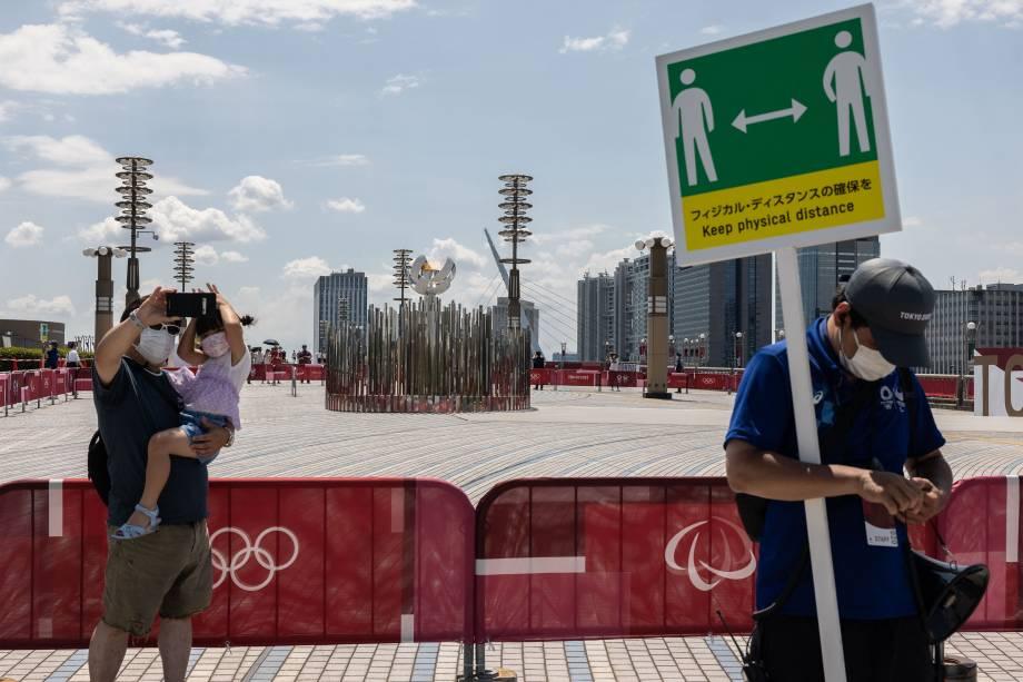 Pessoas fazem selfie em frente a pira Olímpia, na Ponte Ariake Yume-no-Ohashi, em Tóquio, durante os Jogos Olímpicos -
