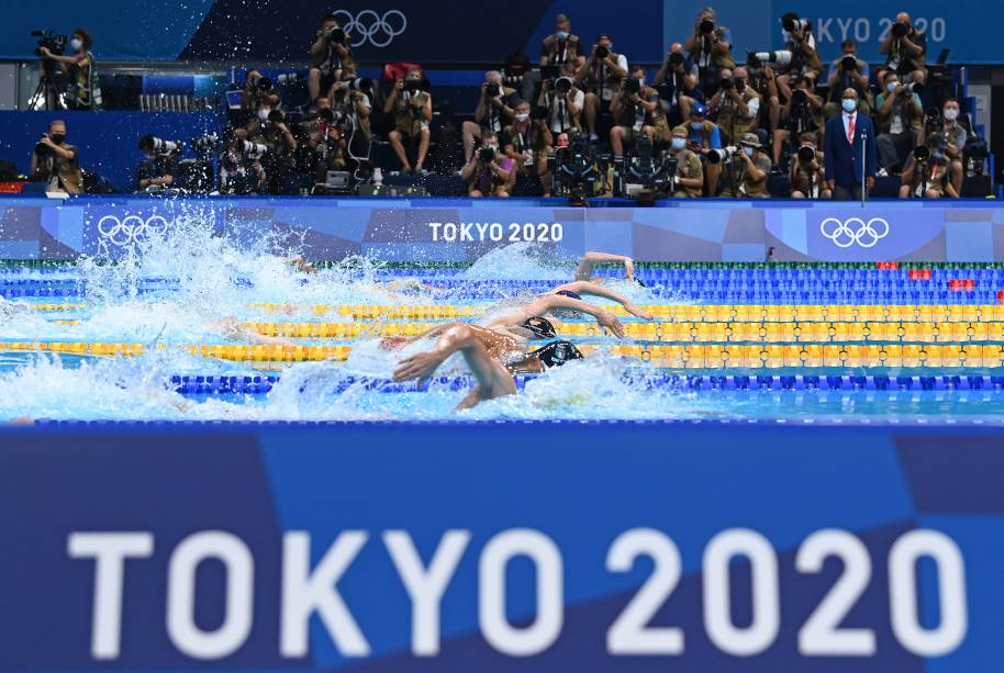 Com fotógrafos ao fundo, competidores nadam durante a prova medley individual de 400m -
