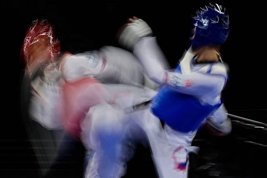 Huang Yu-Jen (azul), de Taiwan, e o iraniano Mirhashem Hosseini em prova do taekwondo masculino -