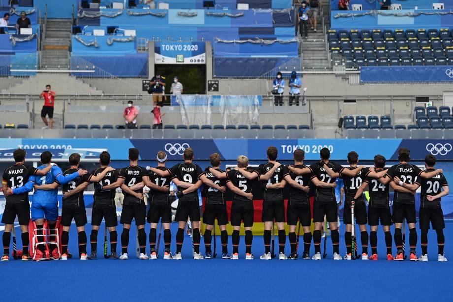 Jogadores da Alemanha ouvem o hino em frente a uma arquibancada quase vazia antes de partida pelo hóquei na grama -